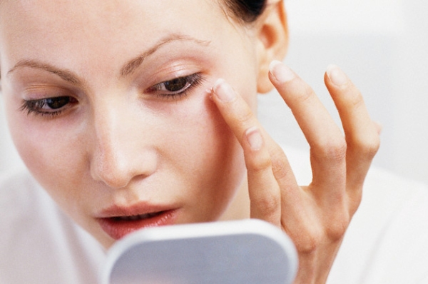 Woman applying eye cream --- Image by © Corbis